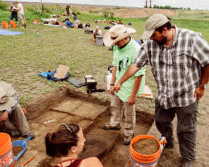 Jason LaBelle working with students at Fossil Creek archaeological site
