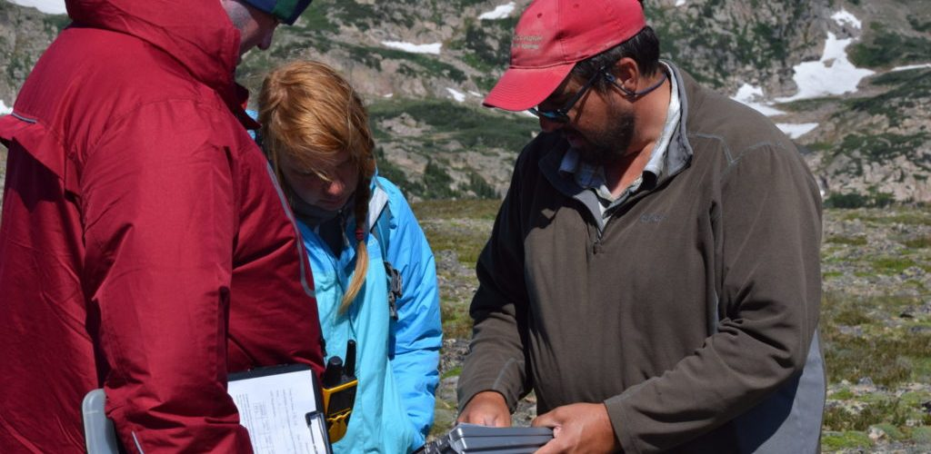 Jason LaBelle showing data to students out in the field