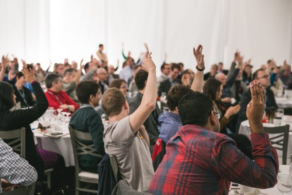 Students raise their hands in participation at a Center for Public Deliberation event