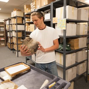 Colorado State University Archaeology student Michael Troyer looks at a specimen in the Archaeological Repository.