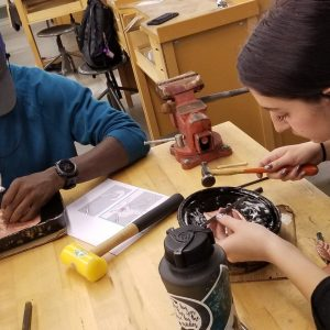 Two students working on a metalsmithing project
