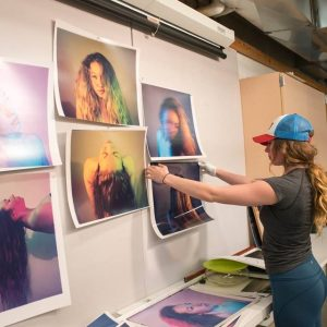 Student hanging photos as part of her Photo Imaging Making degree