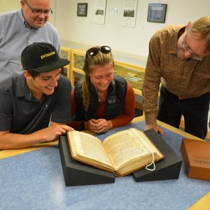 Students and faculty gather over a historical book written in Spanish