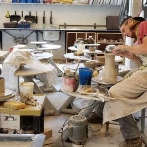Two students making clay pots