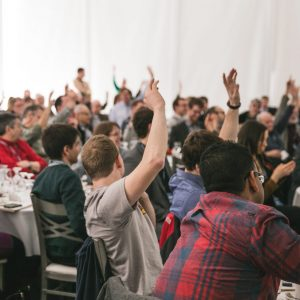 Group of people raising their hands in a facilitated discussion