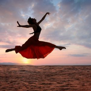 Dancer leaping in scenic sunset backdrop