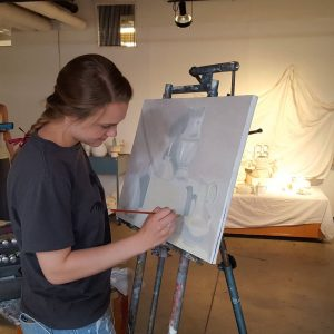 Student painting a still life