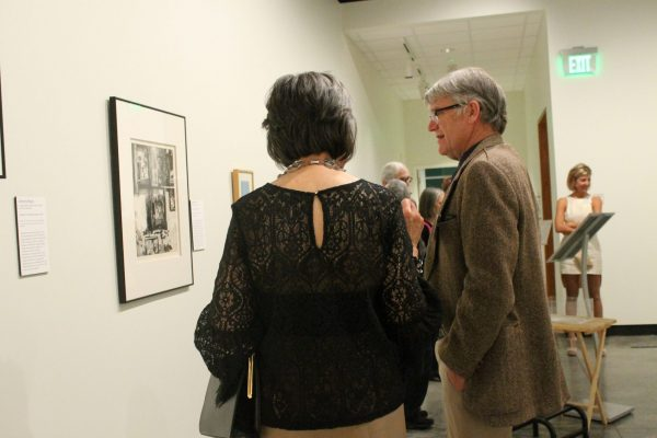 Attendees look at a piece of art