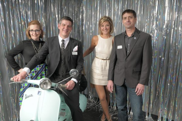 People pose for a photo with a vespa and a silver background
