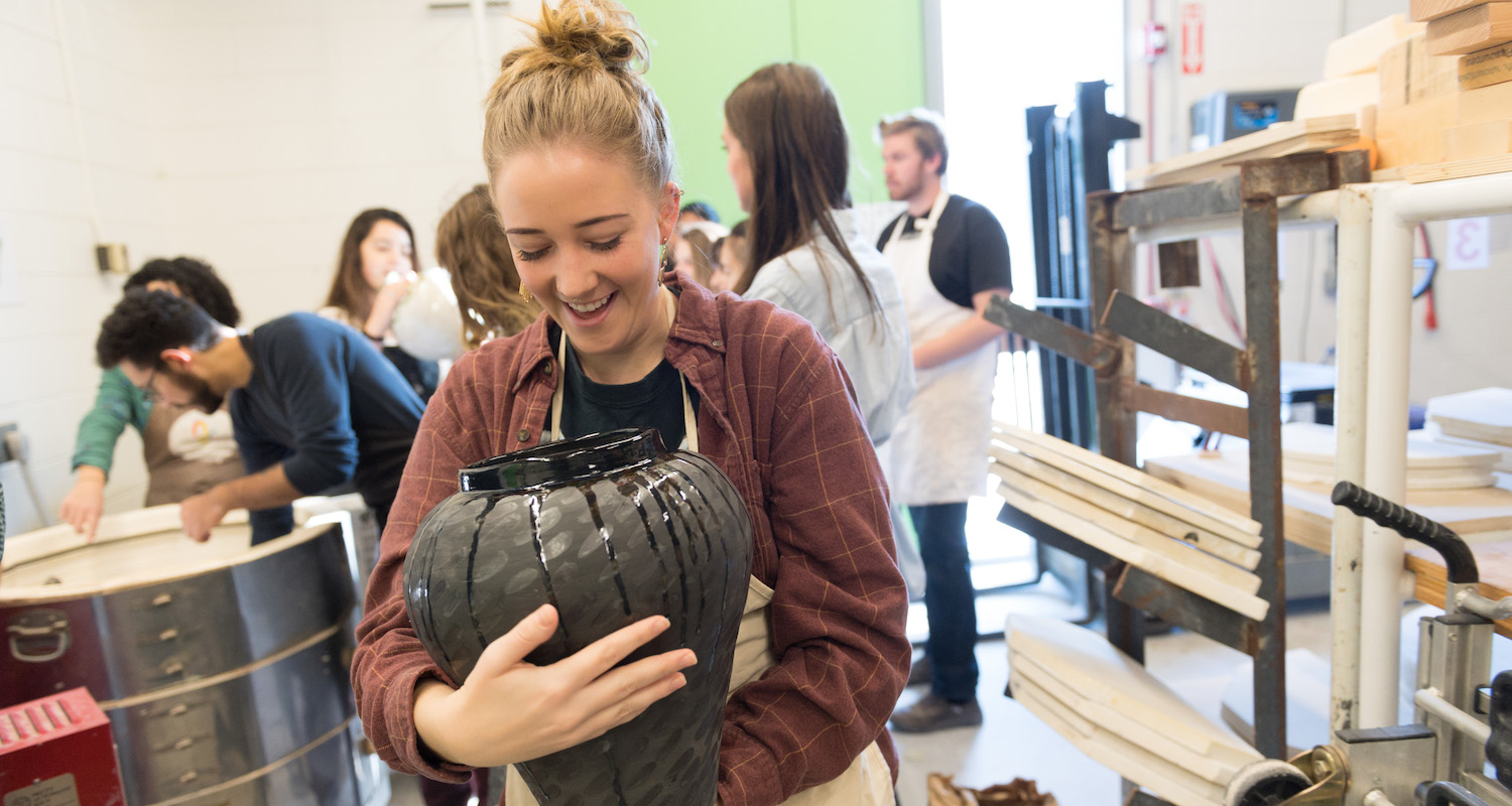 Katie McNaught smiles as she pulls her pottery out of the kiln in Sanam Emami's class.
