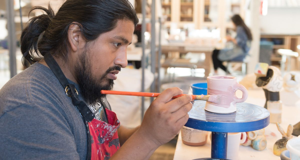 Saxon Martinez applies glaze to a cup in Sanam Emami's pottery class, December 4, 2018.