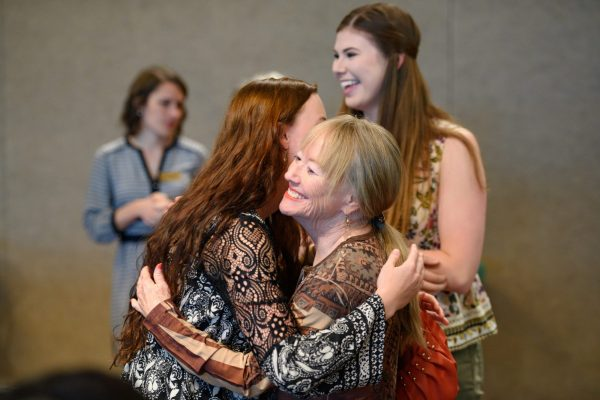 A scholarship recipient and donor hug at the event