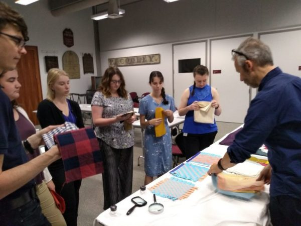 Cozart alongside other Deerfield fellows examining textiles