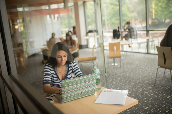 Student with a laptop open sitting in the behavioral sciences building at CSU