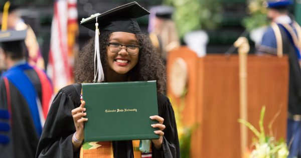 Student proudly holding up her diploma cover at College of Liberal Arts commencement